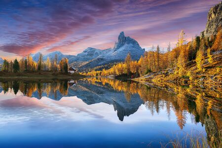 Wonderfull autumn view of  Lake Federa in Dolomites  at sunset. Fantastic autumn scene with colour sky, majestic rocky mount and colorful trees glowing sunlight in Dolomites. Location: Federa lake with Dolomites peak, Cortina DAmpezzo, South Tyrol, Dolomites, Italy, Europe Reklamní fotografie