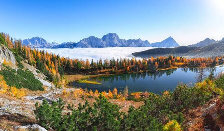 Wonderfull autumn view with colour sky, majestic rocky mount and colorful trees glowing sunlight of  Lake Federa in Dolomites . Location: Federa lake with Dolomites peak, Cortina DAmpezzo, South Tyrol, Dolomites, Italy
