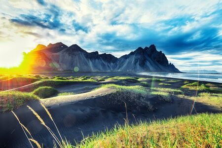 Dramatic sunny day and gorgeous rippled black sand beach and green grass on Stokksnes cape in Iceland. Reklamní fotografie