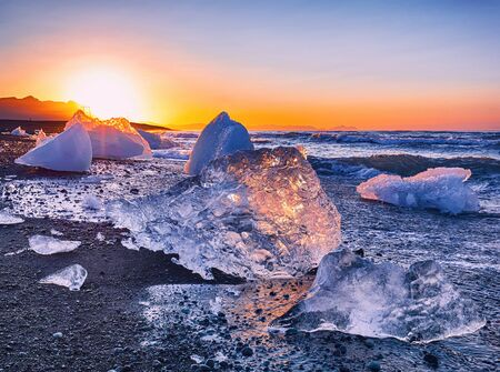 Incredible pieces of the iceberg sparkle on famous Diamond Beach at  Jokulsarlon lagoon during sunset. Location : Jokulsarlon lagoon, Diamond beach, Vatnajokull national park, Iceland, Europe Banco de Imagens - 130806426