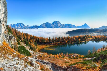 Stunning aerial view of  crystal clear Lake Federa in Dolomites Alps under sunlight in mist and fog. Fantastic autumn sunrise in Dolomites. Location: Federa lake with Dolomites peak, Cortina DAmpezzo, South Tyrol, Dolomites, Italy, Europe Reklamní fotografie