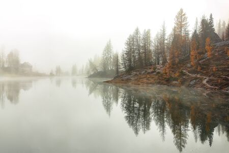 Dramatic foggy autumn landscape. View on Federa Lake early in the morning at autumn. Location: Federa lake with Dolomites peak, Cortina DAmpezzo, South Tyrol, Dolomites, Italy, Europe Banco de Imagens - 130806604