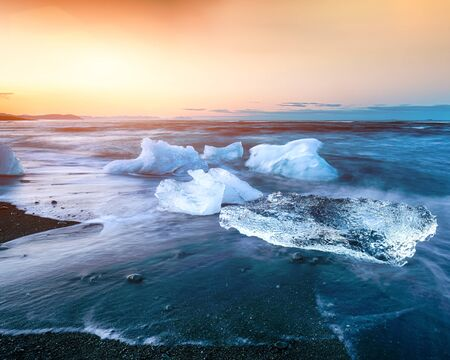 Incredible pieces of the iceberg sparkle on famous Diamond Beach at  Jokulsarlon lagoon during sunset. Location : Jokulsarlon lagoon, Diamond beach, Vatnajokull national park, Iceland, Europe Banco de Imagens - 130806607