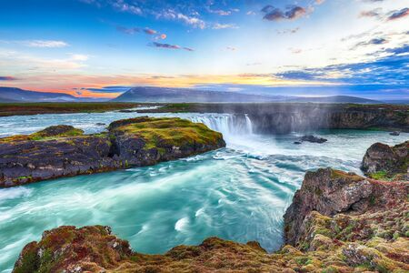 Fantastyczna scena o zachodzie słońca z potężnym wodospadem Godafoss. Dramatyczne niebo nad Godafoss. Lokalizacja: dolina Bardardalur, rzeka Skjalfandafljot, Islandia, Europa
