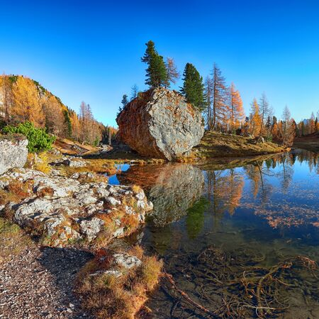 Wonderfull autumn view of  Lake Federa in Dolomites . Fantastic autumn scene with colour sky, majestic rocky mount and colorful trees glowing sunlight in Dolomites. Location: Federa lake with Dolomites peak, Cortina DAmpezzo, South Tyrol, Dolomites, Italy, Europe