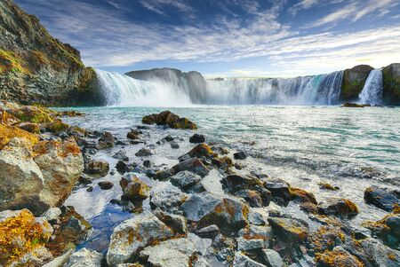 Fabulous scene of powerful Godafoss waterfall. Rocks at foreground. Location: Bardardalur valley, Skjalfandafljot river, Iceland, Europe