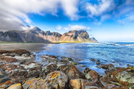 Fantastic sunny day and dramatic black sand beach on Stokksnes cape in Iceland. Banco de Imagens - 130806798