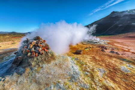 Steaming cone in Hverir geothermal area with boiling mudpools and steaming fumaroles in Iceland  Location: geothermal area Hverir, Myvatn region, North part of Iceland, Europe