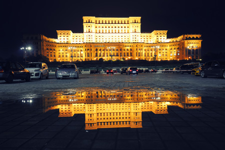 Illuminated Palace of the Parliament of  Bucharest at night. Mirror reflection in water of Palace of the Parliament Bucharest city, Romania, Europe Foto de archivo - 132886338