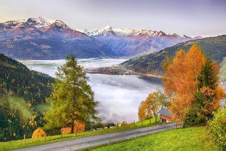Spettacolare vista autunnale degli alberi e delle montagne dei prati del lago a Sell Am See. Fantastica alba sul lago. Luogo: Zell am See, Salisburghese, Austria, Europa Archivio Fotografico
