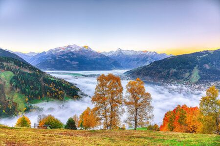 Spectacular autumn view of lake meadows trees and mountains in Sell Am See. Fantastic sunrise over lake. Location: Zell am See, Salzburger Land, Austria, Europe
