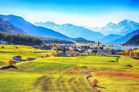 Magnificent autumn view of St.Valentin village and Haidersee (Lago della Muta) lake with Ortler peak on background.Location: Lago della Muta or Haidersee, South Tyrol province, Region Trentino-Alto Adige, Italy, Europe