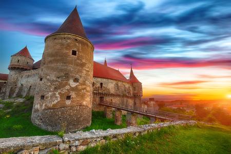 Beautiful panorama of the Hunyad Castle / Corvin's Castle with wooden bridge. Fantastic summer sunset in Hunedoara, Transylvania, Romania, Europe Foto de archivo - 134189362