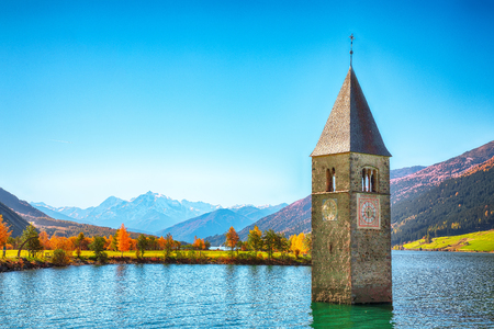 Fantasic autumn view of submerged bell tower in lake Resia.Location: Graun im Vinschgau village, Lago di Resia or Reschensee, South Tyrol province, Region Trentino-Alto Adige, Italy, Europe Editorial