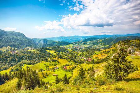 Stunning alpine landscape with green fields and Piatra Craiului mountains in Dambovicioara Commune. Location: Podu Dambovitei village, Arges County, Dambovicioara Commune, Romania, Europe