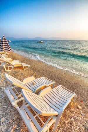 Sun loungers and beach umbrellas at sunset on the beach of Gradac in Makarska riviera. Location: Gradac, Makarska riviera, Dalmatia, Croatia, Europe Reklamní fotografie