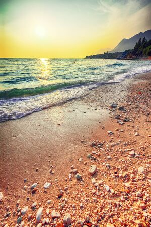 Sunset overview across the beautiful beach of Gradac in Makarska riviera. Location: Gradac, Makarska riviera, Dalmatia, Croatia, Europe