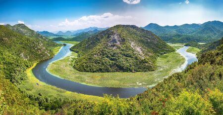 Fantastic view of the Crnojevic river bend around green mountain peaks on a sunny day. Location: National park Skadar Lake, Montenegro, Balkans, Europe.