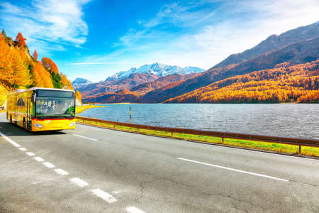 Fantastic autumn scene on Sils Lake (Silsersee) and asphalt road in the front. Colorful autumn scene of Swiss Alps. Location: Maloya, Engadine region, Grisons canton, Switzerland, Europe.
