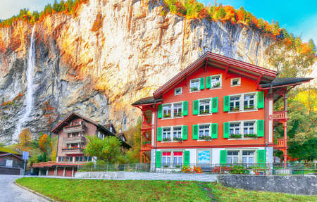 Fantastic autumn view of Lauterbrunnen village with awesome waterfall  Staubbach  in the background.  Location: Lauterbrunnen village, Berner Oberland, Switzerland, Europe. Stock Photo