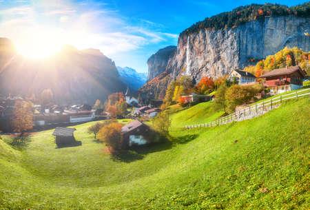 Astonishing autumn view of Lauterbrunnen valley with gorgeous Staubbach waterfall and Swiss Alps in the background. Location: Lauterbrunnen village, Berner Oberland, Switzerland, Europe.