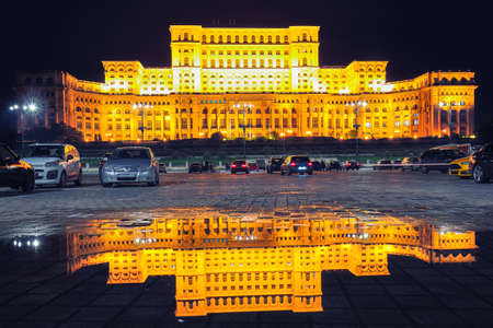 Illuminated Palace of the Parliament of  Bucharest at night. Mirror reflection in water of Palace of the Parliament Bucharest city, Romania, Europe Editorial