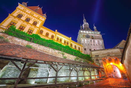 Splendid evening view of medieval city. Night view of historic town Sighisoara and Clock Tower built by Saxons, Transylvania, Romania, Europe