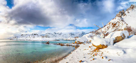 Stunning winter scenery with lots of snow in small fishing village and snowy mountain peaks near Valberg. Location: Valberg, Vestvagoy, Lofotens, Norway
