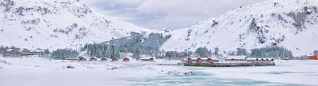 Winter scene with traditional Norwegian red wooden houses on the shore of Rolvsfjord in Valberg on Vestvagoy island at Lofotens. Location: Vestvagoy, Rolvsfjord, Lofoten islands, Norway, Europe.