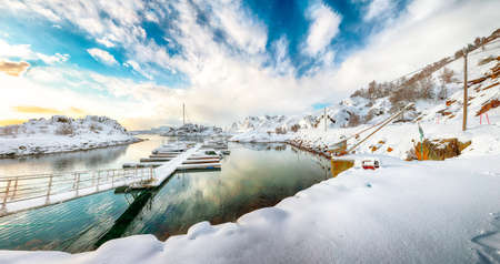 Charming winter scenery with yachts and boats nier pier in small fishing village and snowy mountain peaks near Valberg. Location: Valberg, Vestvagoy, Lofotens, Norway Stock Photo