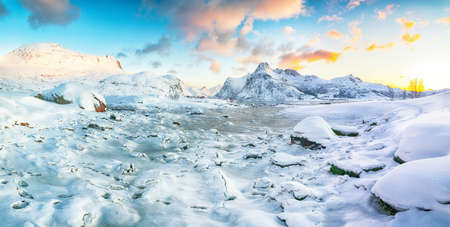 Gorgeous frozen Flakstadpollen and Boosen fjords with cracks on ice during sunrise with Hustinden mountain on background. Location: Flakstadoya island, Lofoten; Norway, Europe Banco de Imagens