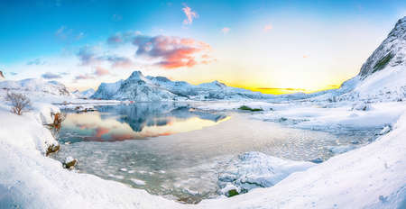 Fabulous frozen Flakstadpollen and Boosen fjords and reflection in water during sunrise with Hustinden mountain on background. Location: Flakstadoya island, Lofoten; Norway, Europe Banco de Imagens