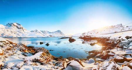Astonishing winter view on Sundstraumen strait that separates Moskenesoya and Flakstadoya islands. Rocky coastline withe cracked ice. Location: Flakstadoya island Lofoten; Norway, Europe