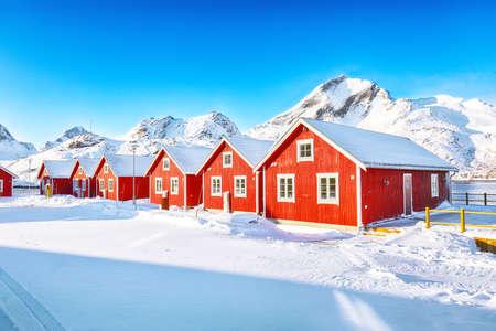 Astonishing winter scenery with traditional Norwegian red wooden houses on the shore of Sundstraumen strait that separates Moskenesoya and Flakstadoya islands. Location: Flakstadoya island, Lofoten; Norway, Europe