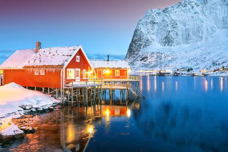 Amazing night cityscape of Reine town with snowy moutaines on background. Popular travel destination on Lofotens. Location: Reine, Lofoten; Norway, Europe