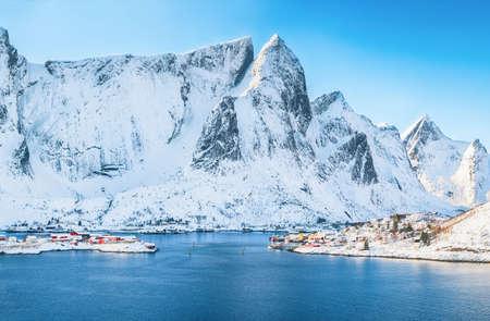 Fabulous winter view of Reine village seen from Olenilsoya island with Hammarskaftet peak and snowy mountaines in background. Location: Olenilsoya island, Lofoten; Norway, Europe