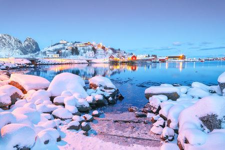 Dramatic evening cityscape of Reine town. Red rorbuers on the shoore of Reinefjorden. Popular travel destination on Lofotens. Location: Reine, Lofoten; Norway, Europe Foto de archivo