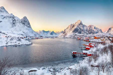 Dramatic evening cityscape of Reine town. Red rorbuers on the shore of Reinefjorden. Popular travel destination on Lofotens. Location: Reine, Lofoten; Norway, Europe