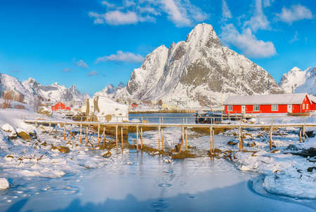 Breathtaking winter sunny view on Reine Village and footbridge above Gravdalbukta bay with cracked ice. Location: Reine, Lofoten; Norway, Europe