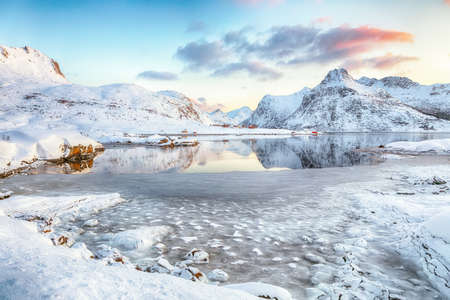 Fabulous frozen Flakstadpollen and Boosen fjords with cracks on ice during sunrise with Hustinden mountain on background. Location: Flakstadoya island, Lofoten; Norway, Europe