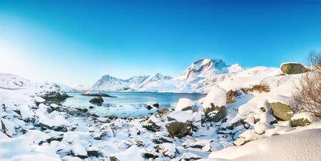 Outstanding winter view on Sundstraumen strait that separates Moskenesoya and Flakstadoya islands. Rocky coastline withe cracked ice. Location: Flakstadoya island Lofoten; Norway, Europe Foto de archivo
