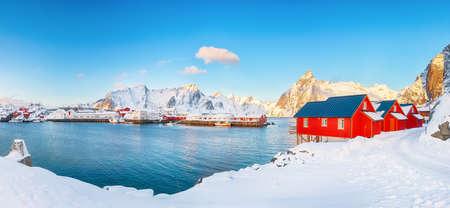 Traditional Norwegian red wooden houses (rorbuer) on the shore of Reinefjorden near Hamnoy village. Olstinden peak on background. Location: Hamnoy, Lofoten; Norway, Europe