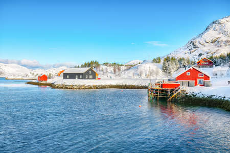 Traditional Norwegian red wooden houses on the shore of Sundstraumen strait that separates Moskenesoya and Flakstadoya islands. Location: Flakstadoya island, Lofoten; Norway, Europe Foto de archivo