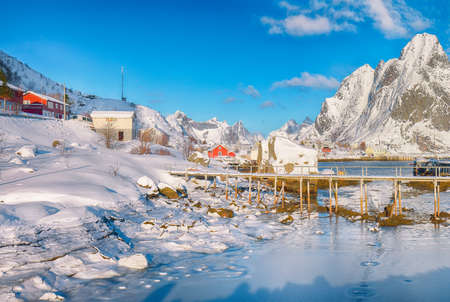 Fabulous winter sunny view on Reine Village and footbridge above Gravdalbukta bay with cracked ice. Location: Reine, Lofoten; Norway, Europe Foto de archivo