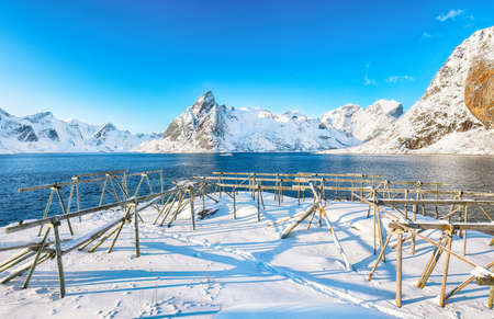 Fantastic winter view on Hamnoy village and Olstinden peak on background. Lots of empty drying racks. Location: Hamnoy, Moskenesoya, Lofoten; Norway, Europe Foto de archivo
