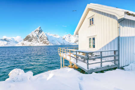 Traditional Norwegian wooden houses on the shore of Reinefjorden on Toppoya island with Olstinden peak and snowy mountaines in background. Location: Toppoya island, Lofoten; Norway, Europe