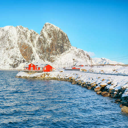 Traditional Norwegian red wooden houses on the shore of Reinefjorden on Toppoya island with Festheltinden peak and snowy mountaines in background. Location: Toppoya island, Lofoten; Norway, Europe