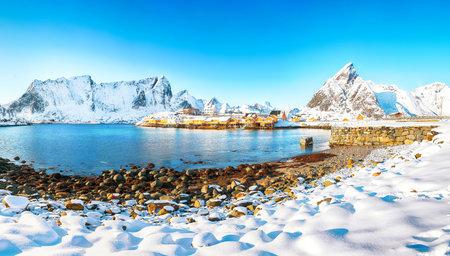Fabulous winter view of Sakrisoy village and snowy mountaines on background. Popular tourist destination on Lofotens. Location: Sakrisoy, Moskenesoya, Lofoten; Norway, Europe