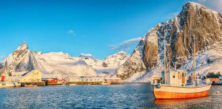 Gorgeous winter view on Hamnoy village with port and Festhaeltinden and Olstinden peaks on background. Location: Hamnoy, Moskenesoya, Lofoten; Norway, Europe