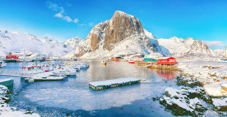 Amazing winter view on Hamnoy village with port and Festhaeltinden mountain on background. Location: Hamnoy, Moskenesoya, Lofoten; Norway, Europe